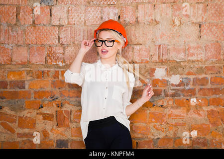 Portrait of architect student or painter with blueprints protect helmet wearing. Brick red background. - Stock Photo