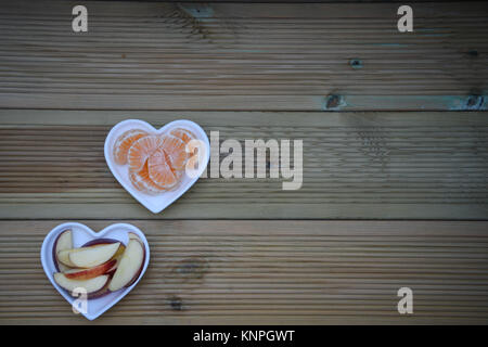 color food photography image of healthy orange fruit pieces sliced apples in white love heart shape dish with rustic - Stock Photo