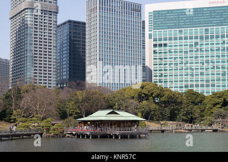 A traditional Japanese tea house in the Hamarikyu Gardens surrounded by City skyscrapers, a public park in Chūō, - Stock Photo