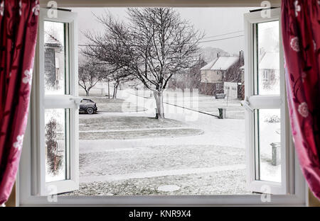 View through open window onto a beautiful winter snow street scene in rural England. Red curtains hang in front - Stock Photo