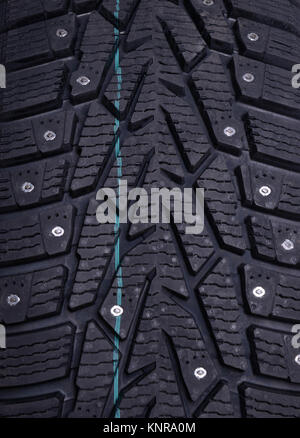 Spikes on a winter tire, close-up - Stock Photo