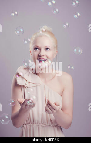 Junge, blonde Frau mit Seifenblasen - young, blond woman with soap bubbles - Stock Photo