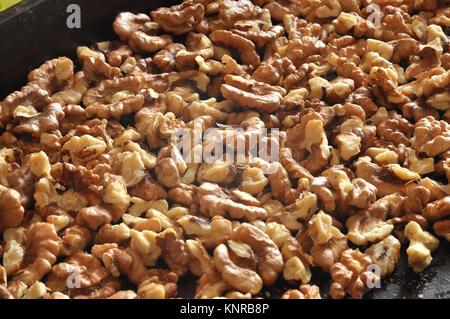 Baked walnut kernels on a black backing tray close-up. Walnut background - Stock Photo