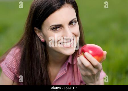 Junge Frau mit Apfel in der Wiese - woman with apple in meadow - Stock Photo