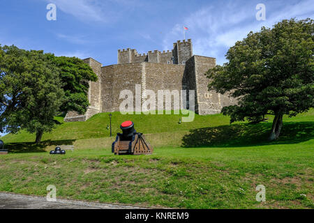 Dover Castle, Dover, Kent, UK - August 17, 2017:  Keep walls with green banks and cannon.  Bright blue sky day. - Stock Photo