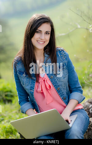 Junge Frau sitzt mit Laptop in der Natur - woman with laptop in nature - Stock Photo