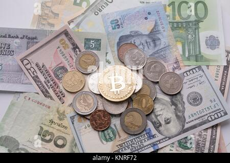 Bitcoin on bills and coins of different countries - Stock Photo