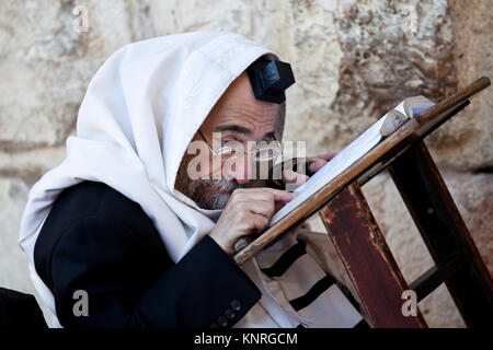 An old orthodox Jew reads a torah at the Western Wall in the center of Jerusalem, Israel - Stock Photo