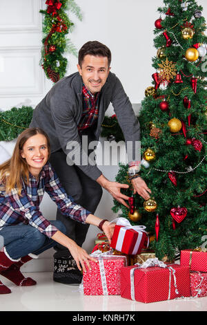 Couple in love sitting next to a nicely decorated Christmas tree, hloding Christmas gifts and smiling - Stock Photo