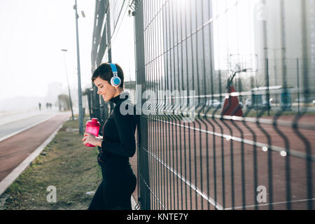 Woman listening to music while working out and jogging outdoor - Stock Photo