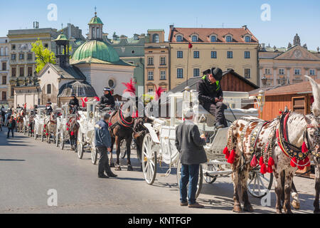 Krakow carriage Poland, view of horse-drawn carriages available for tours of the city of Krakow lined up in the - Stock Photo