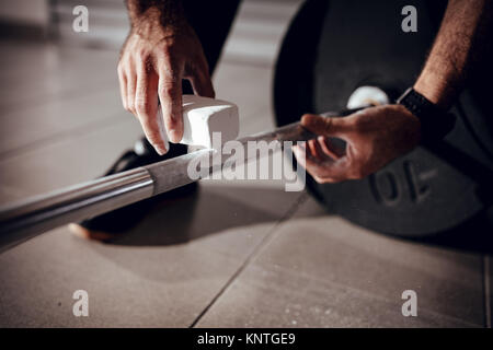 Close-up of a strong man's hands with magnesium powder getting ready to weightlifting at the garage gym. - Stock Photo