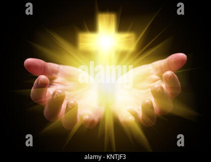 Hands cupped and holding or showing Cross or Crucifix with bright glowing shining light. Christian Christianity - Stock Photo
