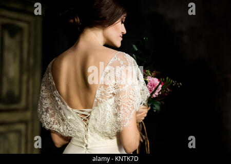 Bride in beautiful dress sitting on chair indoors in dark studio interior like at home. - Stock Photo