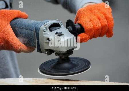 Worker grinds the wood of angular grinding machine - Stock Photo