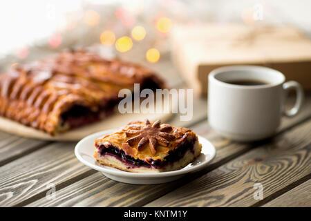 Piece of cake on the Christmas table. Christmas Lights and Decor. Sweets. - Stock Photo