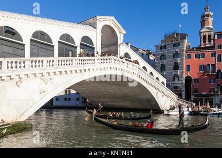 Two gondolas with tourists under the Rialto Bridge, or Ponte di Rialto,  Grand Canal, Venice, Italy in warm evening - Stock Photo