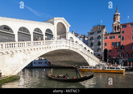 Tourists in a gondola and an Alilaguna waterbus ferry below the Rialto Bridge, or Ponte di Rialto, Grand Canal, - Stock Photo
