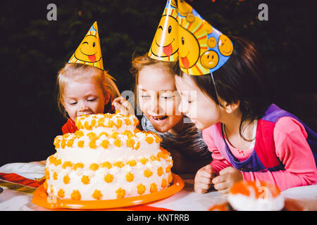 Children's birthday party. Three cheerful children girls at the table eating cake with their hands and smearing - Stock Photo
