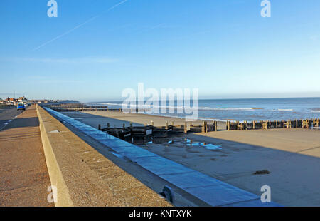 A view of the seawall and beach on a winter afternoon at Walcott, Norfolk, England, United Kingdom. - Stock Photo