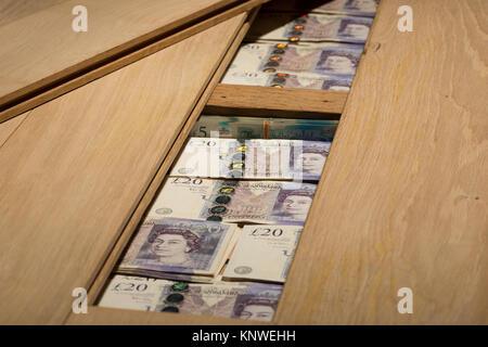 Poor interest bank rates, money £5 £20 hidden under oak wooden floor boards as alternative to safety deposit concealed - Stock Photo