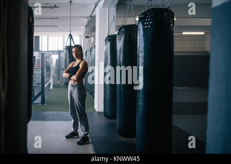 Female boxer standing inside a boxing studio with her hands folded. Woman standing in a boxing training centre with - Stock Photo