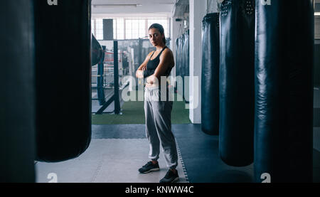 Woman standing in a boxing training centre with punching bags all around. Female boxer standing inside a boxing - Stock Photo