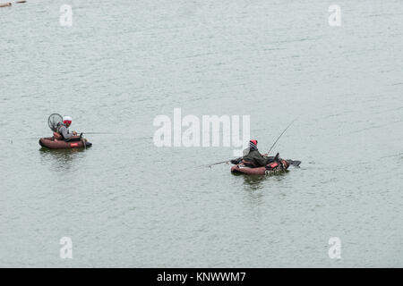 Two fishermen in belly boats in the waters of the Proserpina reservoir, Badajoz, Extremadura, Spain a stormy day. - Stock Photo