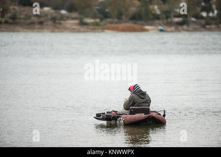 A fisherman in a belly boat in the waters of the Proserpina reservoir, Badajoz, Extremadura, Spain a stormy day. - Stock Photo
