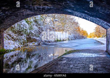 View of frozen Birmingham Canal under a bridge - Stock Photo