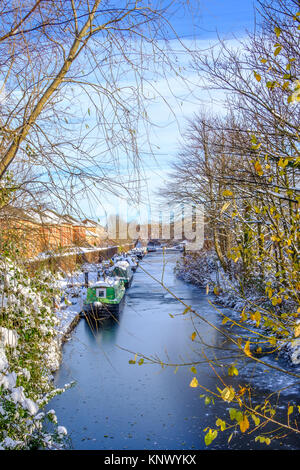 Snow covered canal boats seen in frozen Birmingham canal. - Stock Photo