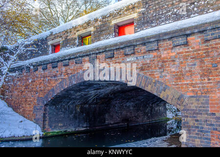 View of frozen Birmingham Canal and a bridge made of bricks - Stock Photo