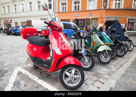 Regensburg, Germany - May 5, 2017: Colorful Vespa scooters stand in a row on a parking lot in old European town - Stock Photo