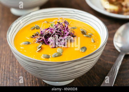 Spicy Squash Soup, gardnished with radish sprouts and pumpkin seeds. - Stock Photo