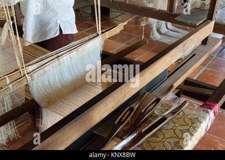 Natural silk farming and handcrafted manufacture of silk artifacts -ladies handweaving on traditional looms ancient - Stock Photo