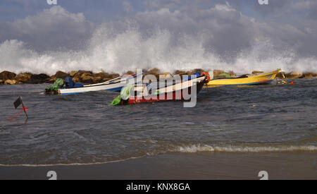 Boats red, yellow and white colors on the ocean, high waves. - Stock Photo