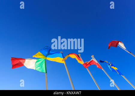 European flags of Italy, Ukraine, Germany, Poland, Sweden and France flying on flag poles against clear blue sky - Stock Photo