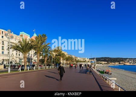 People walking in the sunshine on the seafront promenade parallel to Promenade des Anglais, Nice, Cote d'Azur, France - Stock Photo