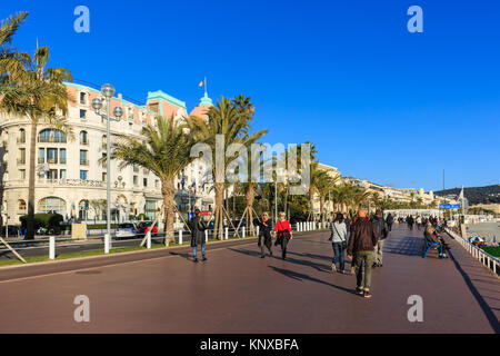 People walking in the sunshine on the seafront Promenade, Boulevard des Anglais, Nice, Cote d'Azur, France - Stock Photo