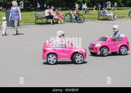 Two little boys driving toy electric cars in a park at sunny summer day in Vilnius, Lithuania - Stock Photo