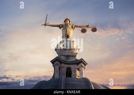Gold Lady Justice Statue on the top of the Old Bailey in London, England, with a sunset sky in the background - Stock Photo