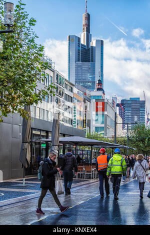 Frankfurt,Germany. People walk in Zeil shopping promenade with outdoor cafe, shops and Commerz Bank High-Rise building - Stock Photo