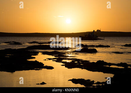 Sunset photo of shipwreck in shallow coastal water in the town of Sal Rei in Boa Vista Island, Cape Verde - Stock Photo