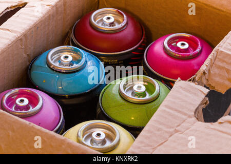 Box full of colored spray cans. - Stock Photo