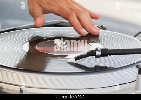 The dj uses vinyl records to mix electronic music and beat rap sound. - Stock Photo