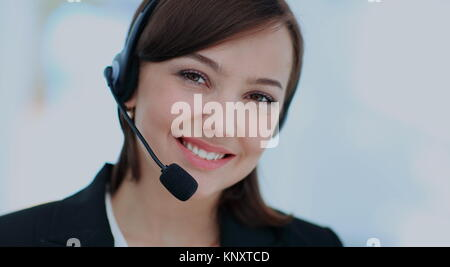Happy young woman working at callcenter, using headset - Stock Photo