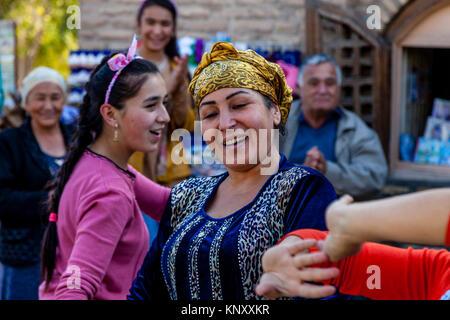 Uzbek Women Dancing In The Street, Khiva, Uzbekistan - Stock Photo