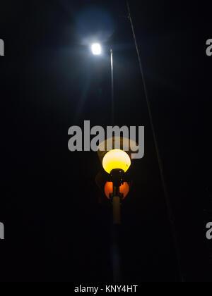 light pole orange lamp at night turned on street urban; essex; england; uk - Stock Photo