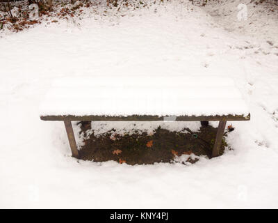 wooden covered public bench snow outside winter grass covered white; essex; england; uk - Stock Photo