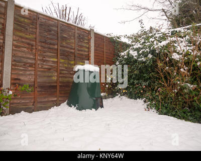 snow in back garden on green bin lid and fence and floor; essex; england; uk - Stock Photo